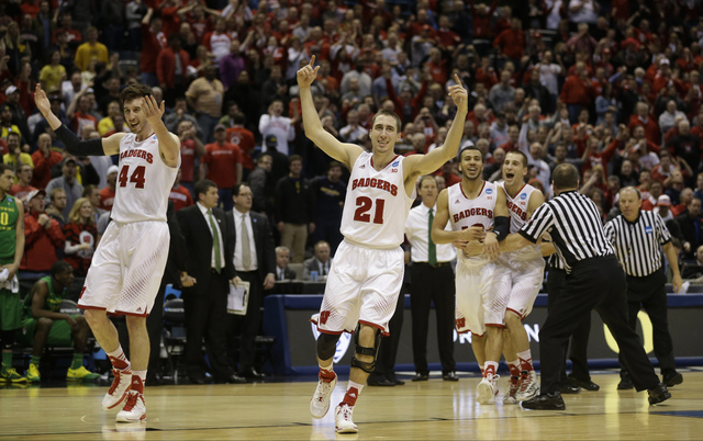 Wisconsin forward Frank Kaminsky (44) and Wisconsin guard Josh Gasser (21) celebrate  during the second half of a third-round game against the Oregon in the NCAA college basketball tournament Satu ...