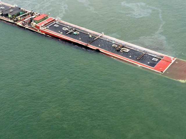 In this image provided by the U.S. Coast Guard a barge loaded with marine fuel oil sits partially submerged in the Houston Ship Channel, Saturday March 22, 2014. The bulk carrier Summer Wind, repo ...