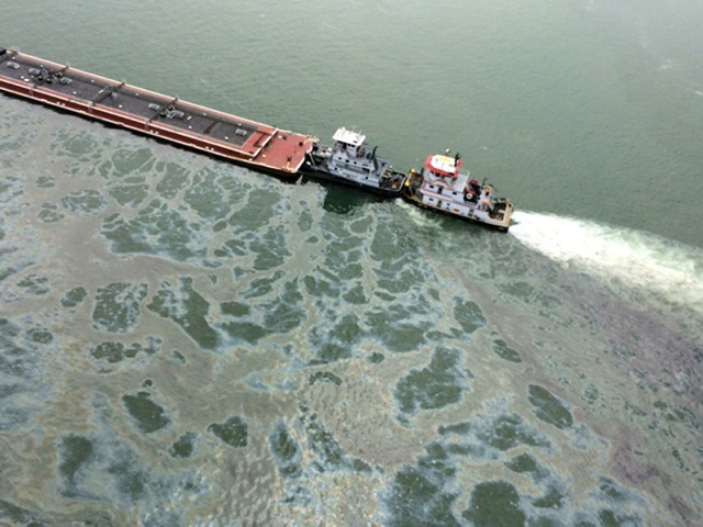 A barge loaded with marine fuel oil sits partially submerged in the Houston Ship Channel, March 22, 2014. The bulk carrier Summer Wind, reported a collision between the Summer Wind and the barge,  ...