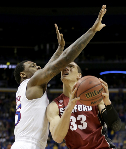 Stanford's Dwight Powell (33) shoots under pressure from Kansas's Tarik Black during the first half of a third-round game at the NCAA college basketball tournament Sunday, March 23, 2014, in St. L ...