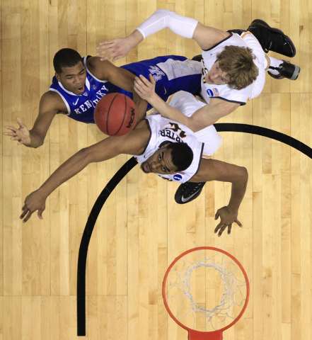 Kentucky's Aaron Harrison, top left, shoots as Wichita State's Ron Baker, top right, and Darius Carter defend during the first half of a third-round game of the NCAA college basketball tournament  ...
