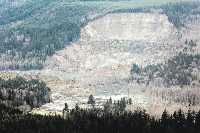 In this aerial photo taken Saturday, March 23, 2014, a massive mudslide is shown in between the towns of Darrington, Wash., and Arlington, Wash. The slide killed at least three people and many peo ...