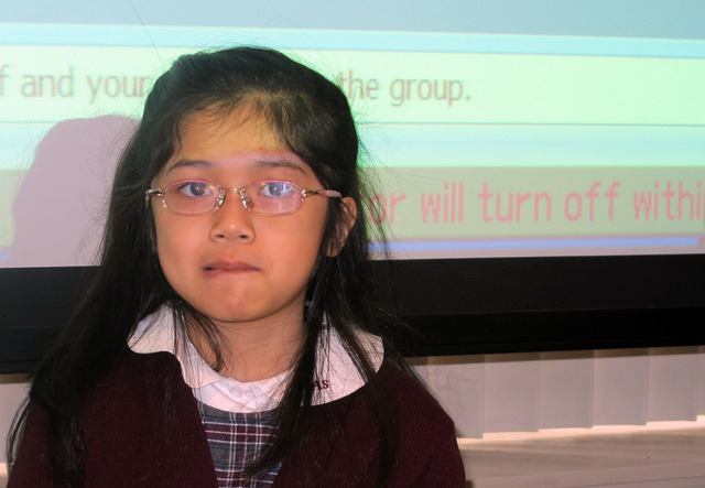 In this Tuesday, Feb. 25, 2014, photo, third-grader Andrea Esteban tries to imitate the droopy smile of a stroke victim at Montefiore Hospital in the Bronx borough of New York. The hospital teache ...