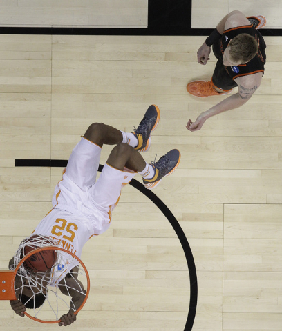 Tennessee guard Jordan McRae (52) dunks against Mercer forward Jakob Gollon (20) during the first half of an NCAA college basketball third-round tournament game, Sunday, March 23, 2014, in Raleigh ...