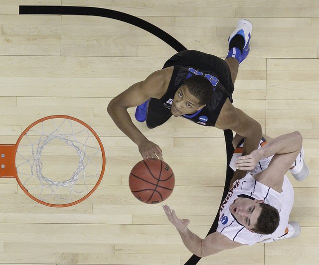 Virginia guard Joe Harris (12) and Memphis guard Geron Johnson (55) wait for a ball during the second half of an NCAA college basketball third-round tournament game, Sunday, March 23, 2014, in Ral ...