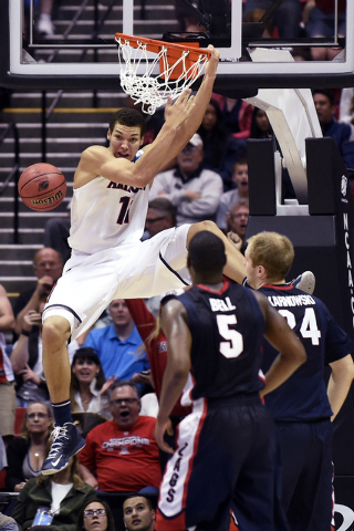 Arizona forward Aaron Gordon hangs on the rim after dunking a basket while playing Gonzaga during the first half of a third-round game in the NCAA college basketball tournament Sunday, March 23, 2 ...