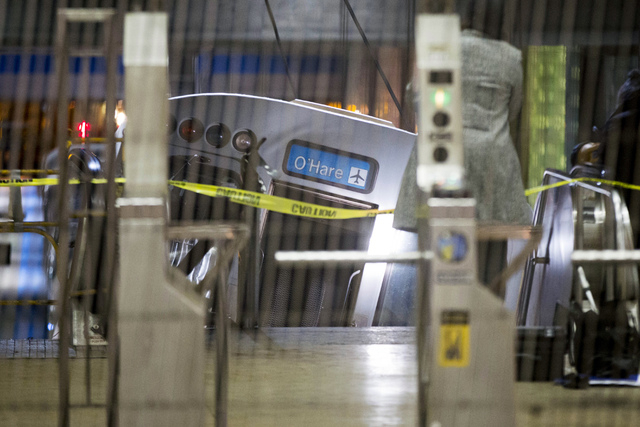 A derailed Chicago Transit Authority train car rests on an escalator at the O'Hare Airport station early Monday in Chicago. More than 30 people were injured after the eight-car train plowed across ...