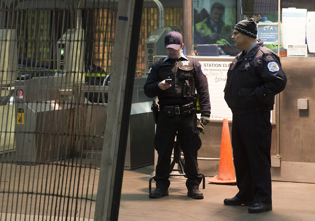 Chicago Police work the scene where a Chicago Transit Authority derailed at the O'Hare Airport station early Monday in Chicago. More than 30 people were injured after the eight-car train plowed ac ...