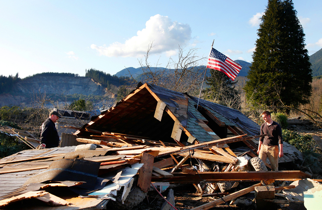 Brian Anderson, left,  and Coby Young search through the wreckage of a home belonging to the Kuntz family on Sunday near Oso, Wash. The entire Kuntz family was at a baseball game Saturday morning  ...