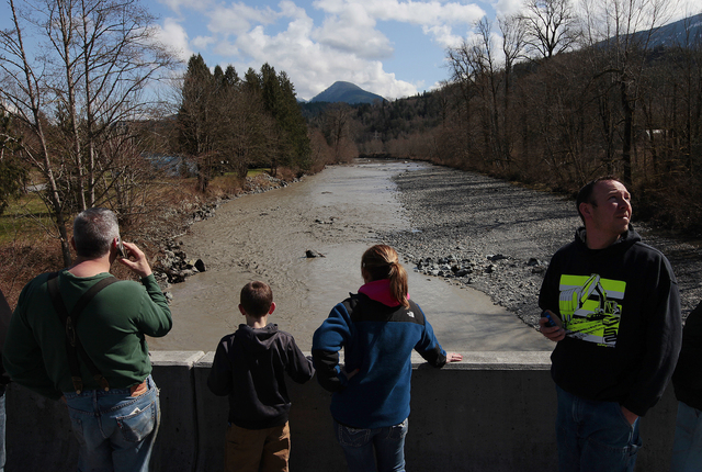 Residents watch as debris comes down the Stillaguamish River from the Whitman Road bridge east of Oso, Wash., on Sunday. (AP Photo /The Herald, Mark Mulligan)