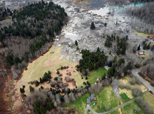 A view of the damage from Saturday's mudslide in Oso, Wash. At least eight people were killed in the 1-square-mile slide that hit in a rural area about 55 miles northeast of Seattle. Several peopl ...