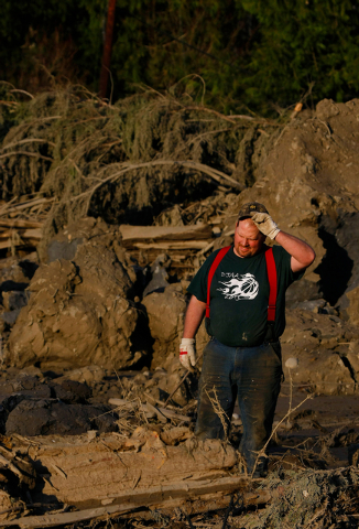 Jason Anderson searches through mudslide rubble for bodies on Cory Kuntz's property on Sunday. The Kuntz family had gone to a baseball game Saturday morning when the fatal slide swept through the  ...