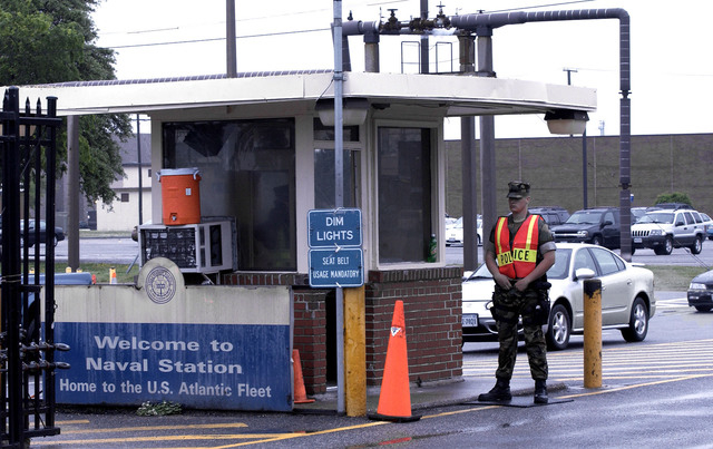 Security personnel wait to inspect vehicles entering Norfolk Naval Station in Norfolk, Va. A sailor was fatally shot at the world's largest naval base late Monday, and security forces killed a mal ...