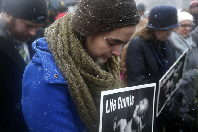 Mary Novick of St. Paul, Minn., bows her head in prayer during a demonstration in front of the Supreme Court in Washington, Tuesday, March 25, 2014, as the court heard oral arguments in the challe ...