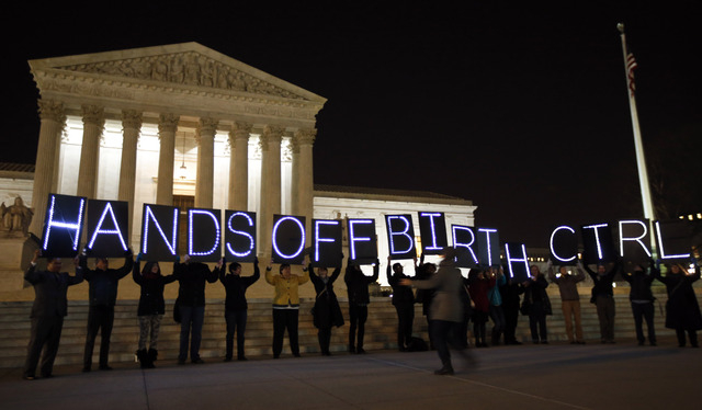 A group of people organized by the NYC Light Brigade and the women's rights group UltraViolet use letters in lights to spell out their opinion, in front of the Supreme Court on Monday in Washingto ...