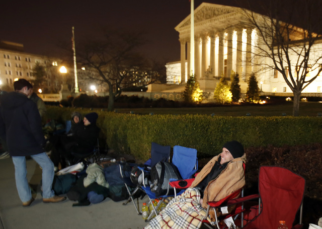 Jerome Weaver, from Vineland, N.J., waits in line in front of the Supreme Court on Monday in Washington. The Supreme Court is weighing whether corporations have religious rights that exempt them f ...