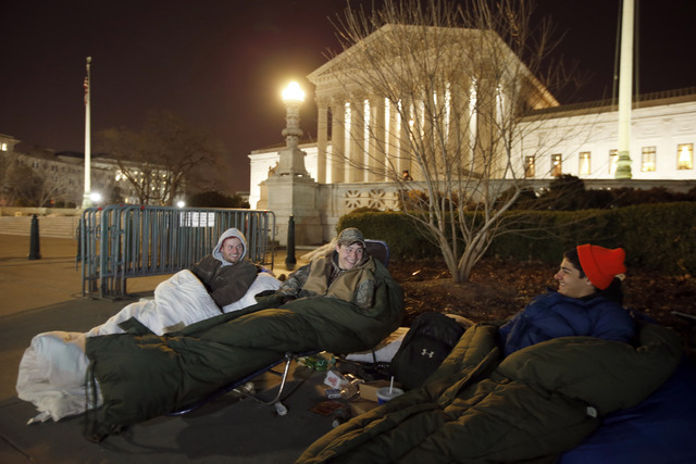 Brandon, left, from Warrenton, Va., sits with Matt and Zack, both from Nokesville, Va., as they wait in line in front of the Supreme Court on Monday in Washington. The men arrived Friday afternoon ...