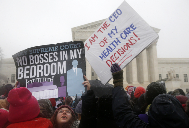 Demontrators gather in front of the Supreme Court in Washington, Tuesday, March 25, 2014, as the court heard oral argument in the challenges of President Barack Obama's health care law requirement ...