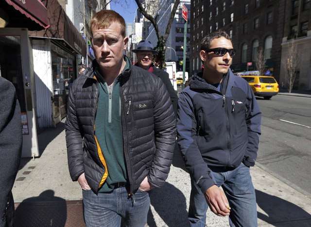 James Brady, left, and Andrew Rossig, right, two parachutists who jumped from One World Trader Center in September 2013, are accompanied by attorney Timothy Parlatore to surrender to police, in Ne ...