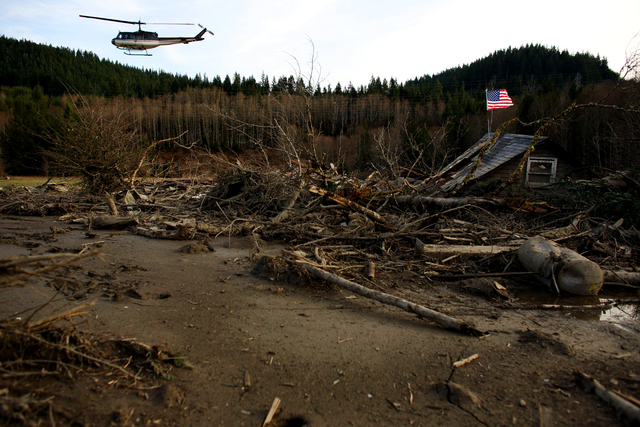 From a helicopter, Snohomish County Sheriff Ty Trenary surveys the wreckage of homes destroyed in Saturday's mudslide, Monday, March 24, 2014, near Oso, Wash. The search for survivors grew Monday  ...