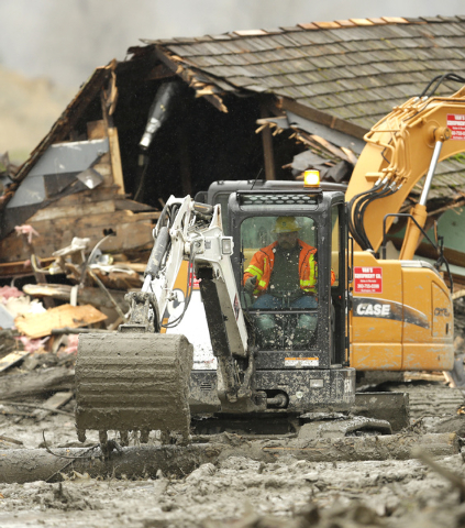 Workers using heavy equipment work to clear debris Tuesday, March 25, 2014, near a destroyed house that came to rest on Washington Highway 530 on the western edge of the  massive mudslide that str ...
