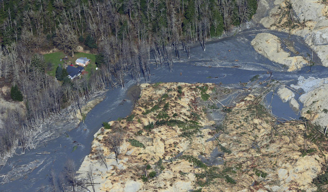 An intact house sits at left at the edge of the massive mudslide that killed at least eight people and left dozens missing is shown in this aerial photo, Monday, March 24, 2014, near Arlington, Wa ...