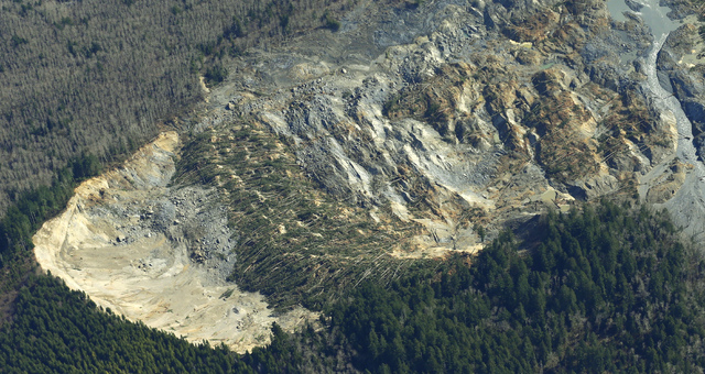 The massive mudslide that killed at least eight people and left dozens missing is shown in this aerial photo, Monday, March 24, 2014, near Arlington, Wash. The search for survivors grew Monday, ra ...