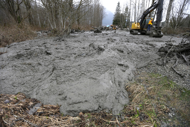 Thick, oozing mud is cleared from Washington Highway 530 by workers using heavy equipment, Tuesday, March 25, 2014, on the western edge of the massive mudslide that struck the area Saturday, killi ...