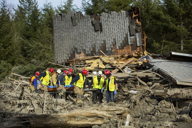 Rescue workers remove a body from the wreckage of homes destroyed by Saturday's mudslide near Oso, Wash, on Monday, March 24, 2014. The search for survivors of Saturday's deadly mudslide grew Mond ...
