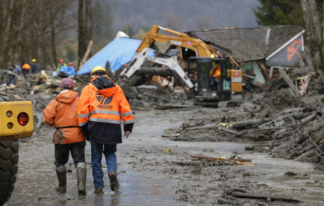 Workers walk through mud as heavy equipment operators work to clear debris Tuesday, March 25, 2014, from Washington Highway 530 on the western edge of the massive mudslide that struck the area Sat ...