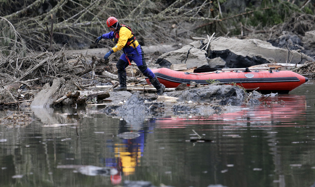 A searcher steps off of his boat to look through debris following a deadly mudslide, Tuesday, March 25, 2014, in Oso, Wash. At least 14 people were killed in the 1-square-mile slide that hit in a  ...