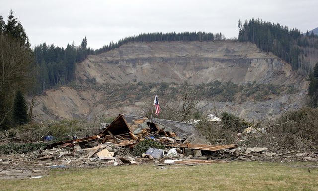 A flag, put up by volunteers helping search the area, stands in the ruins of a home left at the end of a deadly mudslide from the now-barren hillside seen about a mile behind, Tuesday, March 25, 2 ...