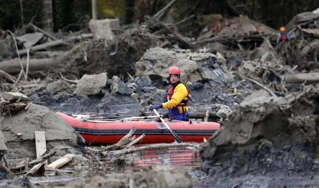 A searcher uses a small boat to look through debris from a deadly mudslide Tuesday, March 25, 2014, in Oso, Wash. At least 14 people were killed in the 1-square-mile slide that hit in a rural area ...