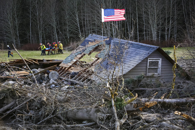 Rescue workers remove a body from the wreckage of homes destroyed by a mudslide near Oso, Wash, Monday, March 24, 2014. The search for survivors of Saturday's deadly mudslide grew Monday to includ ...