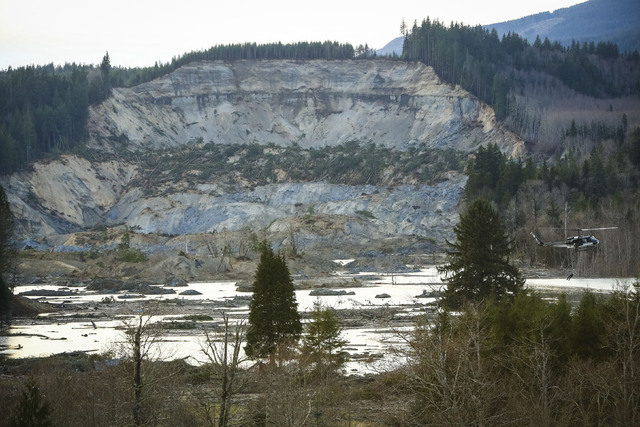 A rescue worker is lowered from a helicopter, right, near Oso, Wash, Monday, March 24, 2014. The search for survivors of Saturday's deadly mudslide grew Monday to include scores of people who were ...
