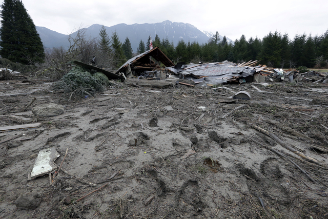 Footprints from searchers remain in mud at the edge of a deadly mudslide Tuesday, March 25, 2014, in Oso, Wash. At least 14 people were killed in the 1-square-mile slide that hit in a rural area a ...