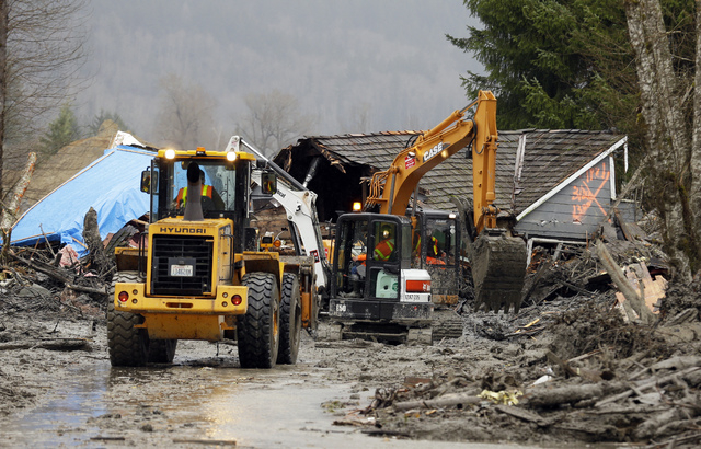 Workers using heavy equipment work to clear debris Tuesday, March 25, 2014, from Washington Highway 530 on the western edge of the  massive mudslide that struck near Arlington, Wash., Saturday, ki ...