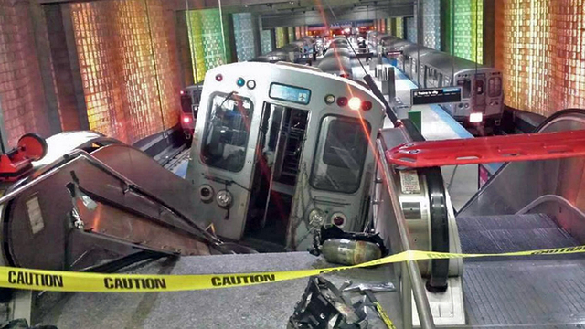 In this March 24, 2014 file photo, a Chicago Transit Authority train car rests on an escalator at the O'Hare Airport station after it derailed early in the morning, injuring more than 30 people, i ...