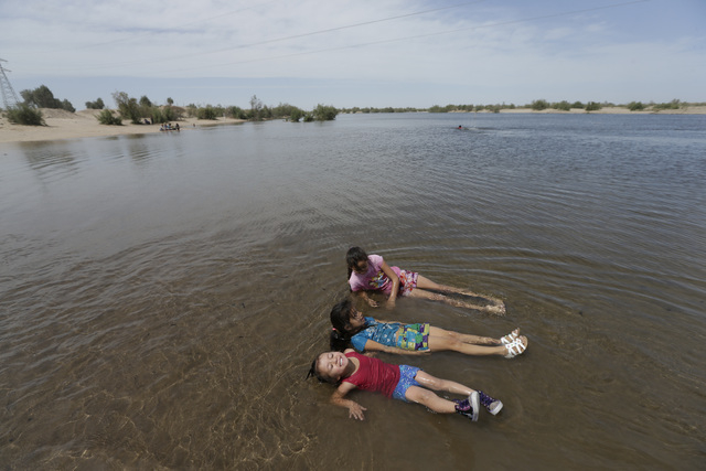 Sisters Patricia Munoz, left, Rosa Munoz, center, and Irma Munoz, right, relax in Colorado river water flowing in a normally dry riverbed Thursday, March 27, 2014, in San Luis Rio Colorado, Mexico ...