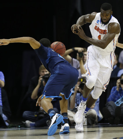 Florida center Patric Young (4) collides with UCLA guard Norman Powell (4) during the first half in a regional semifinal game at the NCAA college basketball tournament, Thursday, March 27, 2014, i ...