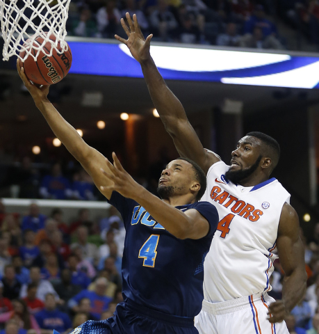 UCLA guard Norman Powell (4) shoots against Florida center Patric Young (4) during the first half in a regional semifinal game at the NCAA college basketball tournament, Thursday, March 27, 2014,  ...