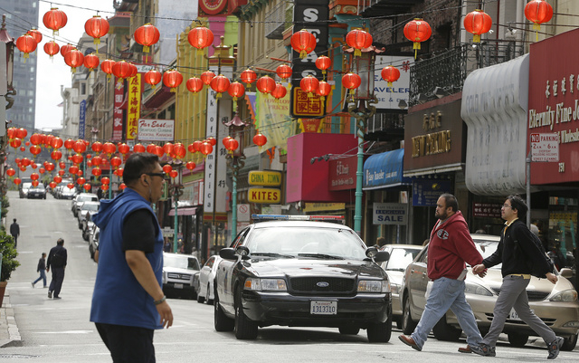 San Francisco police patrol the Chinatown district Thursday, March 27, 2014, in San Francisco. Beneath the strings of red paper lanterns and narrow alleyways of the nation's oldest Chinatown lies  ...