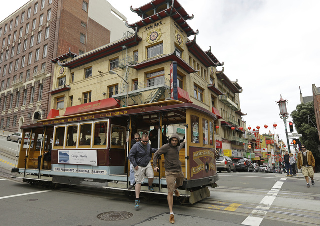 Passengers disembark a cable car in the Chinatown district Thursday, March 27, 2014, in San Francisco. Beneath the strings of red paper lanterns and narrow alleyways of the nation's oldest Chinato ...