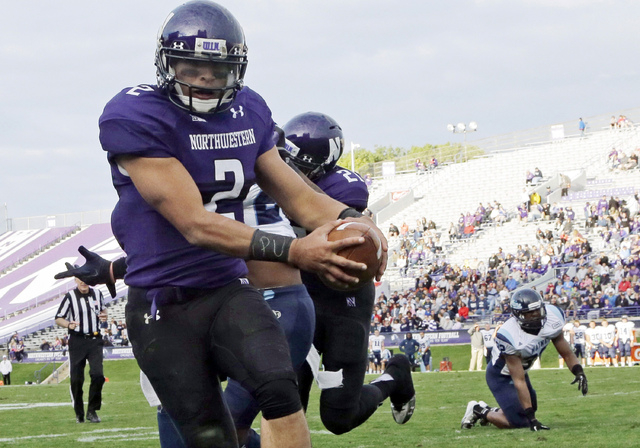 """FILE - In this Sept. 21, 2013, file photo, Northwestern quarterback Kain Colter (2), wears APU for """"All Players United"""" on wrist tape as he scores a touchdown during an NCAA college foot ..."""