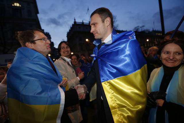 Ukraine's MP Vitali Klitschko, leader of the UDAR (Ukrainian Democratic Alliance for Reform) party, centre right, greets a protester outside 10 Downing Street in London after a meeting with Britis ...