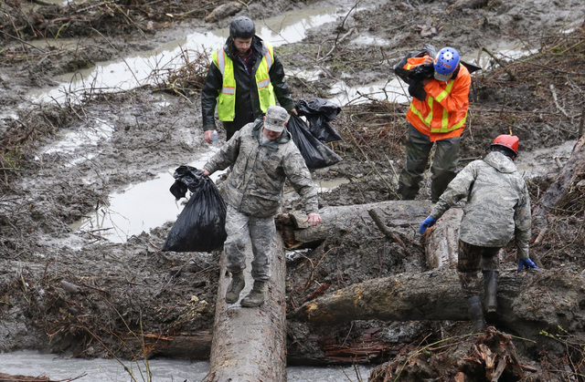 Searchers carry bags of personal belongings collected at the scene of a deadly mudslide Saturday, March 29, 2014, in Oso, Wash. Besides the more than two dozen bodies already found, many more peop ...
