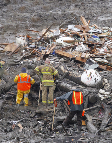 Searchers pause for a moment of silence at the scene of a deadly mudslide Saturday, March 29, 2014, in Oso, Wash. Besides the more than two dozen bodies already found, many more people could be bu ...