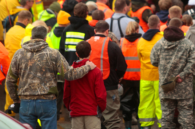 Workers and volunteers observe a moment of silence outside of the Oso Fire Department at 10:37 a.m. Saturday, March 29, 2014, exactly one week after a fatal mudslide struck just east of the small  ...