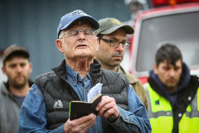 Rev. Michael De Luca offers a prayer before rescue workers and volunteers pause during a state-wide moment of silence to honor the victims of the Oso mud slide in front of the Darrington, Wash., o ...