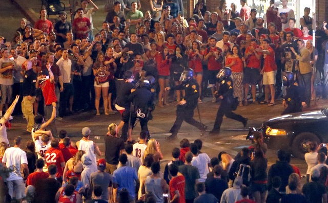 Tucson Police Officers rush out of their line to take a man into custody who had been taunting them and riling up a crowd of fans in Maingate Square, Saturday, March 29, 2014, in Tucson Ariz. foll ...